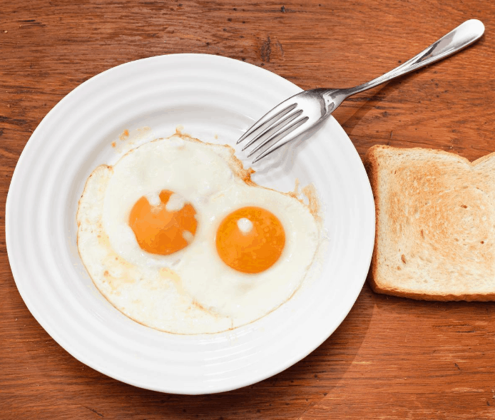 over easy eggs on white plate with piece of toast