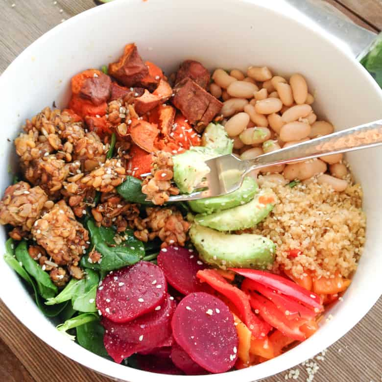 Vegan Buddha Bowl in white bowl with quinoa, tempeh, avocado, beets, peppers, sweet potatoes