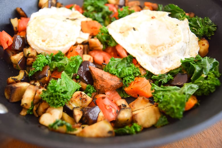 vegetables in a skillet with over easy eggs