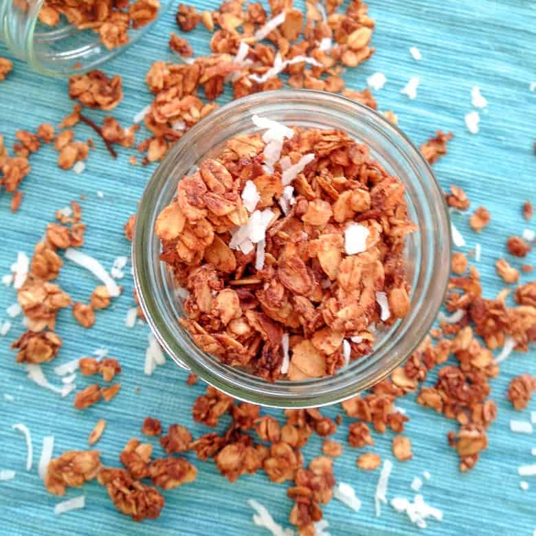 Overhead view of cinnamon maple granola with coconut flakes on blue mat | Bucket List Tummy
