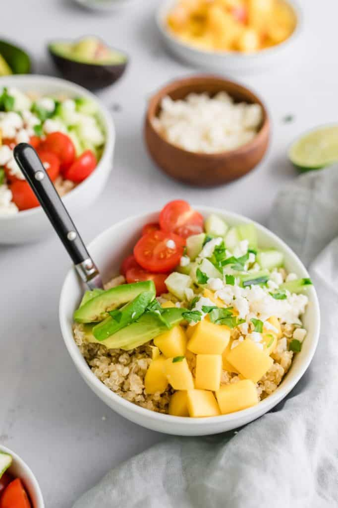 Bowl of summer quinoa salad with sliced mangos, lime and tomatoes with a fork