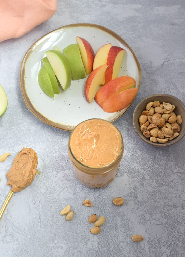 overhead shot of cinnamon peanut butter with apples on plate
