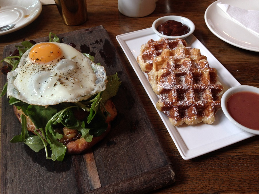 egg plate and liege waffles on white plate on restaurant table