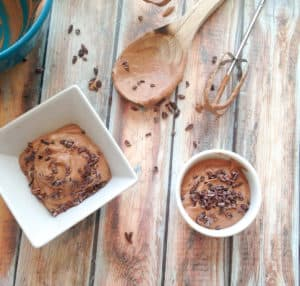 Bowls of chocolate cream pudding with cocoa nibs with mixing spoon