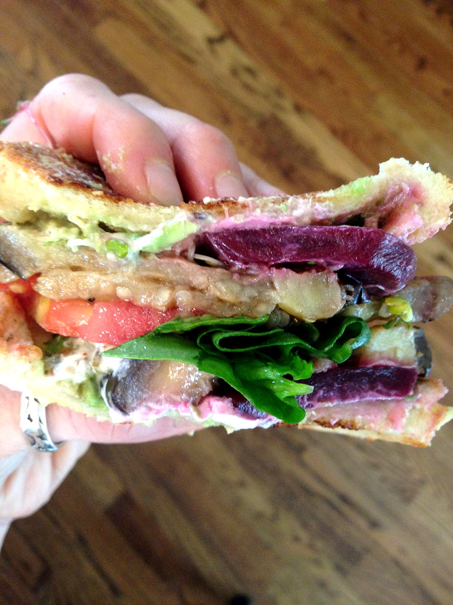 Holding up eggplant goat cheese avocado sandwich with other veggies