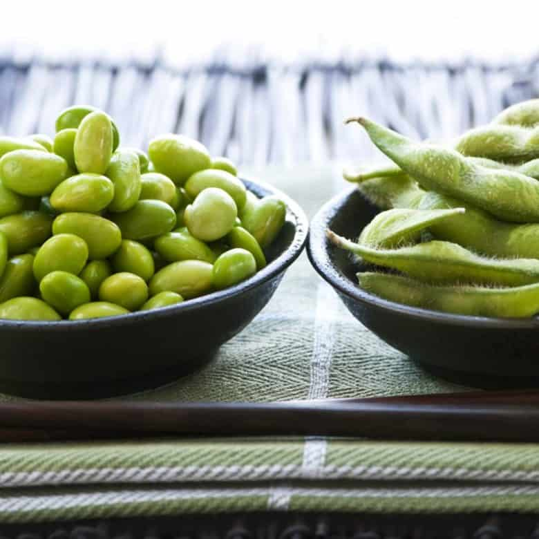 Shelled and unshelled edamame in bowls on table