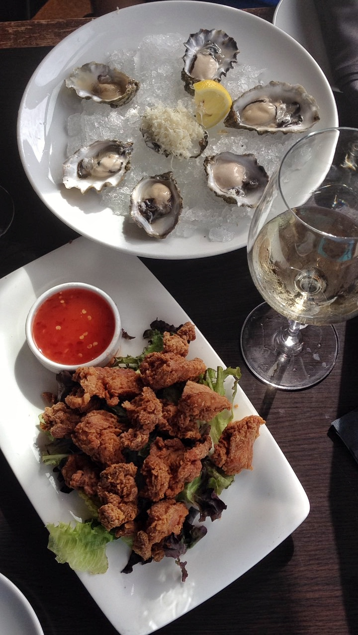 Oysters and calamari on white plates with glass of wine for happy hour
