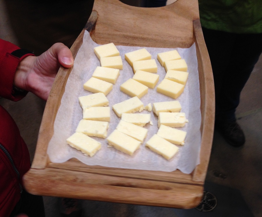 sliced cheese on wooden plate for tasting