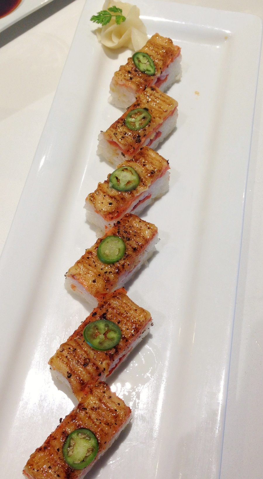 Sushi topped with jalapeno on white plate