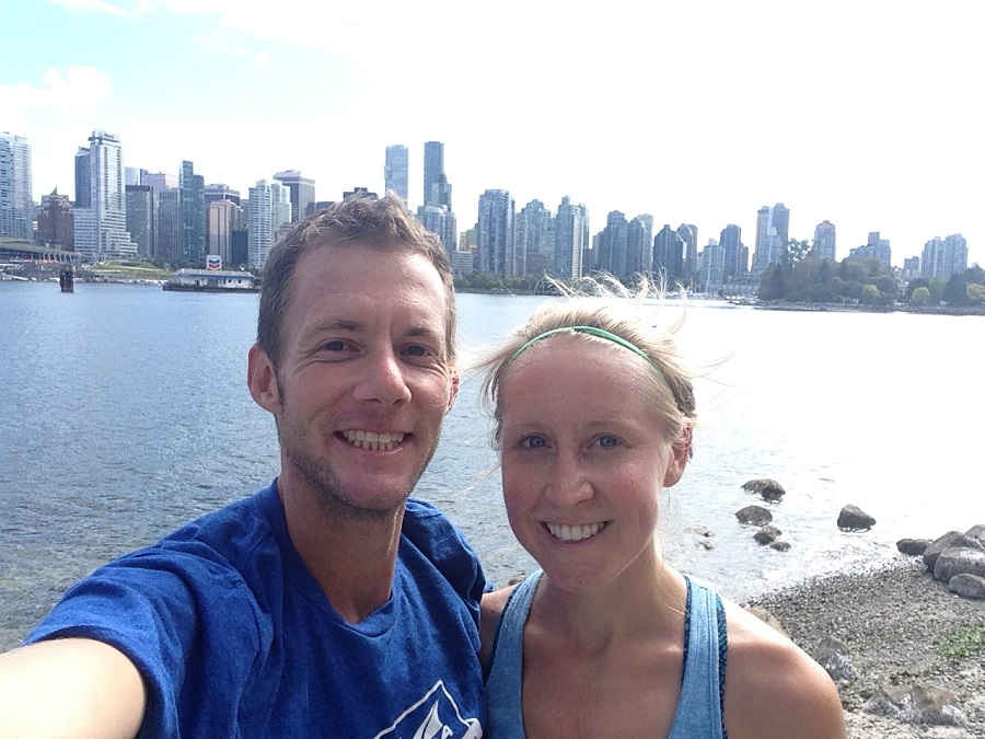 husband and wife posing for pictures on Vancouver Seawall during a run