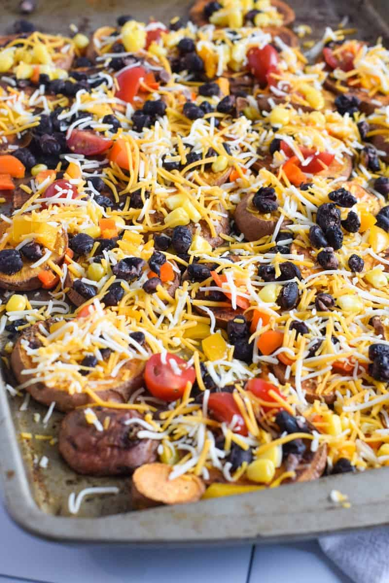 cut sweet potatoes on sheet pan topped with beans, tomatoes and shredded cheese
