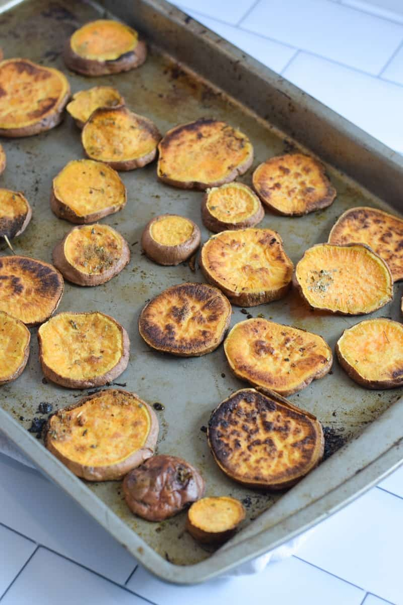 Sweet potato cut into coins roasted on baking sheet
