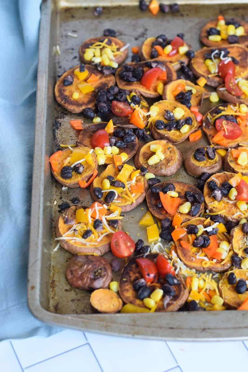 Sheet pan sweet potato nachos on baking pan with blue napkin