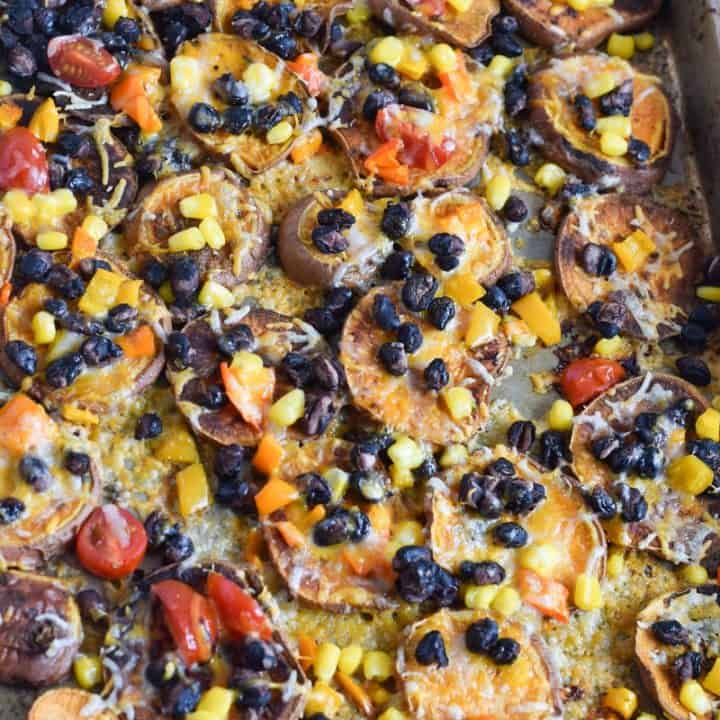 closeup of sweet potato nachos on sheet pan topped with black beans, corn and cheese| Bucket List Tummy