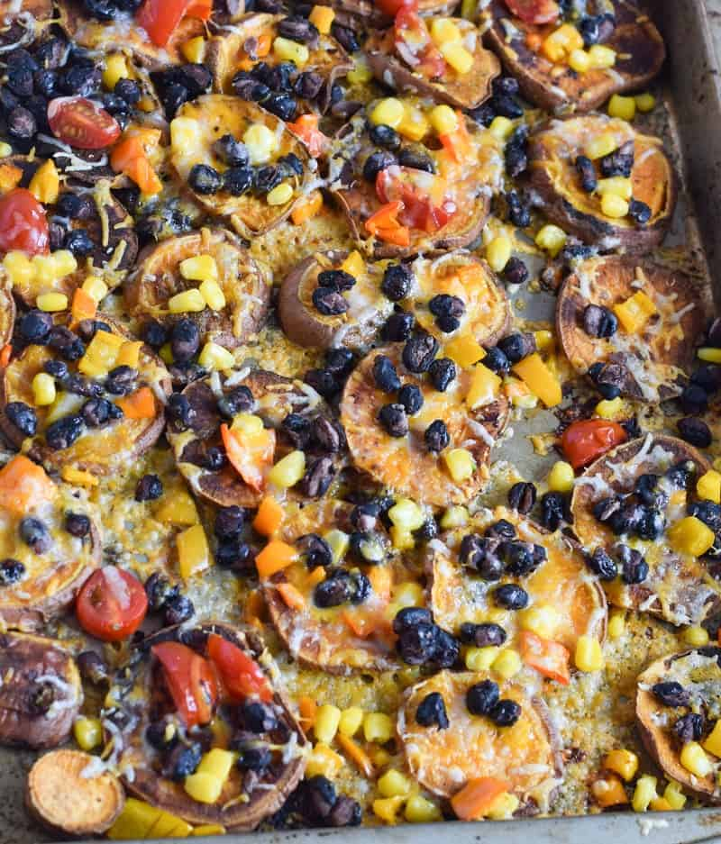 closeup of sweet potato nachos on sheet pan topped with black beans, corn and cheese|