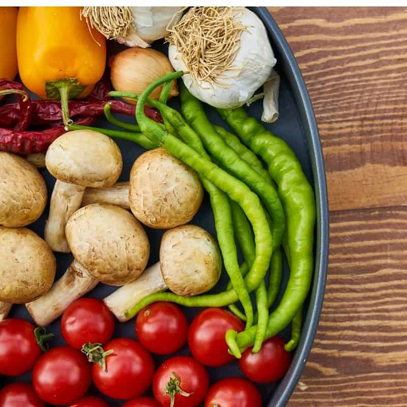 blue bowl of colorful veggies on wooden table