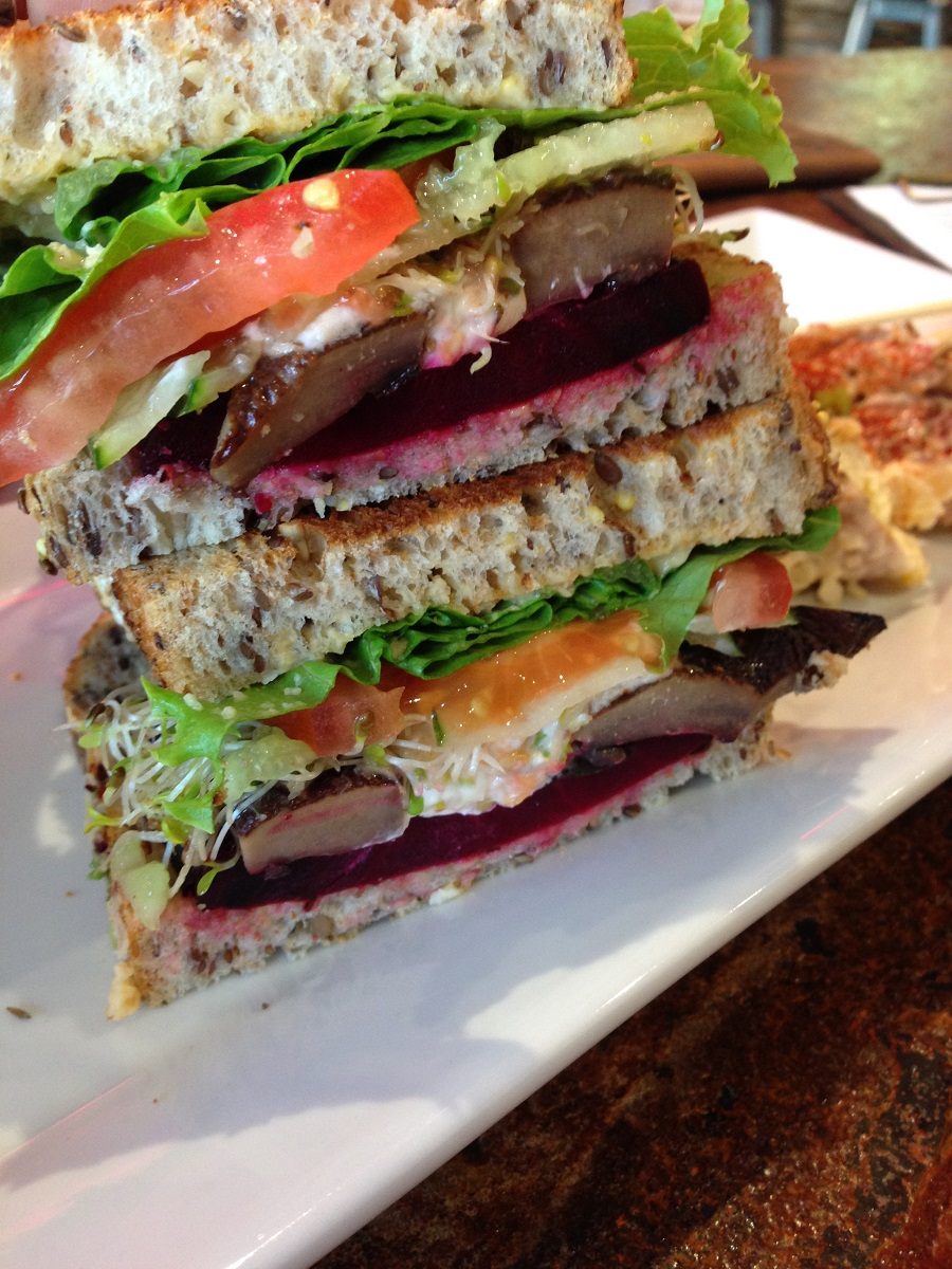 Vegetarian sandwich stacked on white serving plate