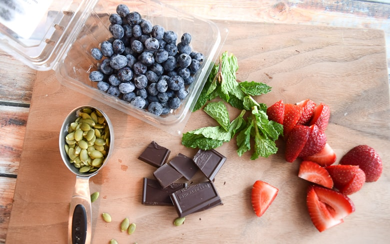 Ingredients to make quinoa breakfast porridge on wooden cutting board