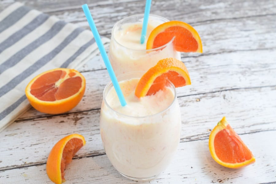 Tropical Creamsicle Smoothie with orange and blue straw on wooden countertop