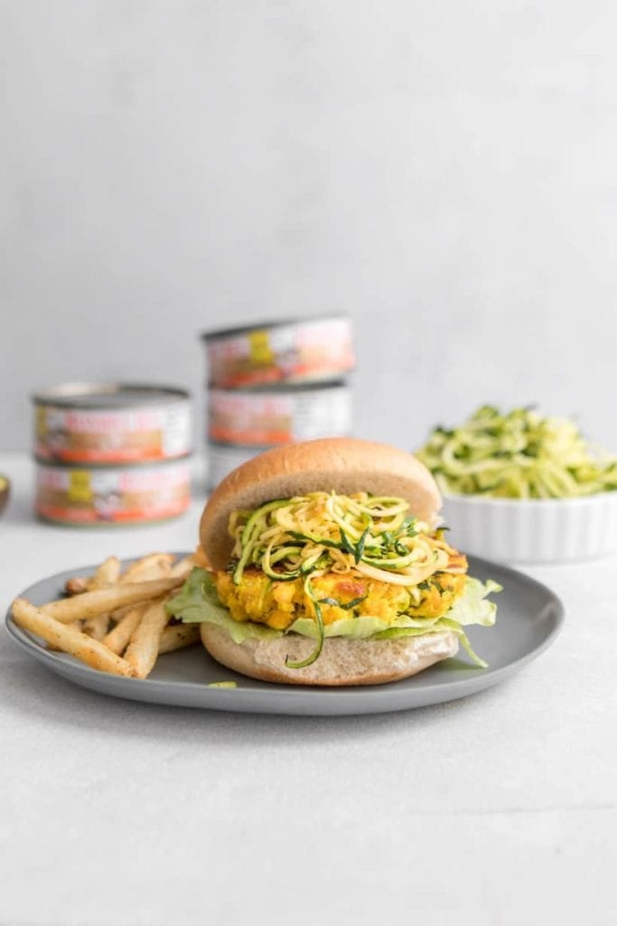 gray plate with fries and salmon burger with spiralized zucchini on a bun
