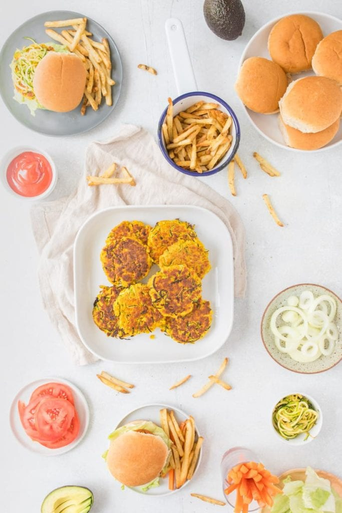 overhead view of table with zucchini turmeric salmon patties on white plate with fries and side of tomatoes and ketchup