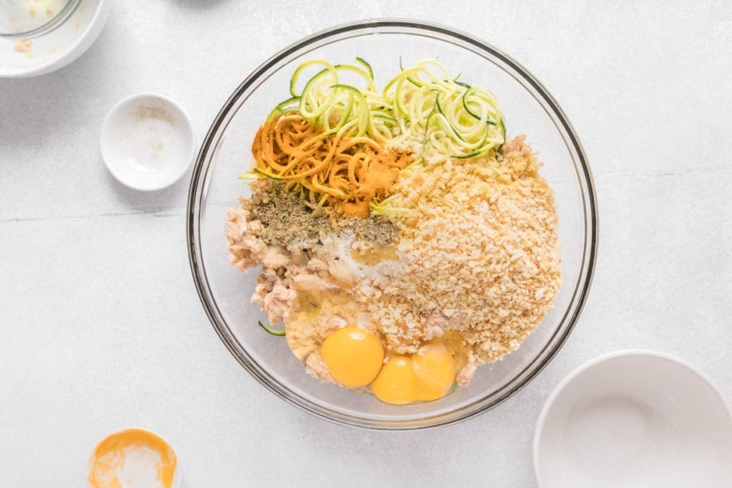 clear bowl with canned salmon, zucchini, eggs and breadcrumbs before mixing
