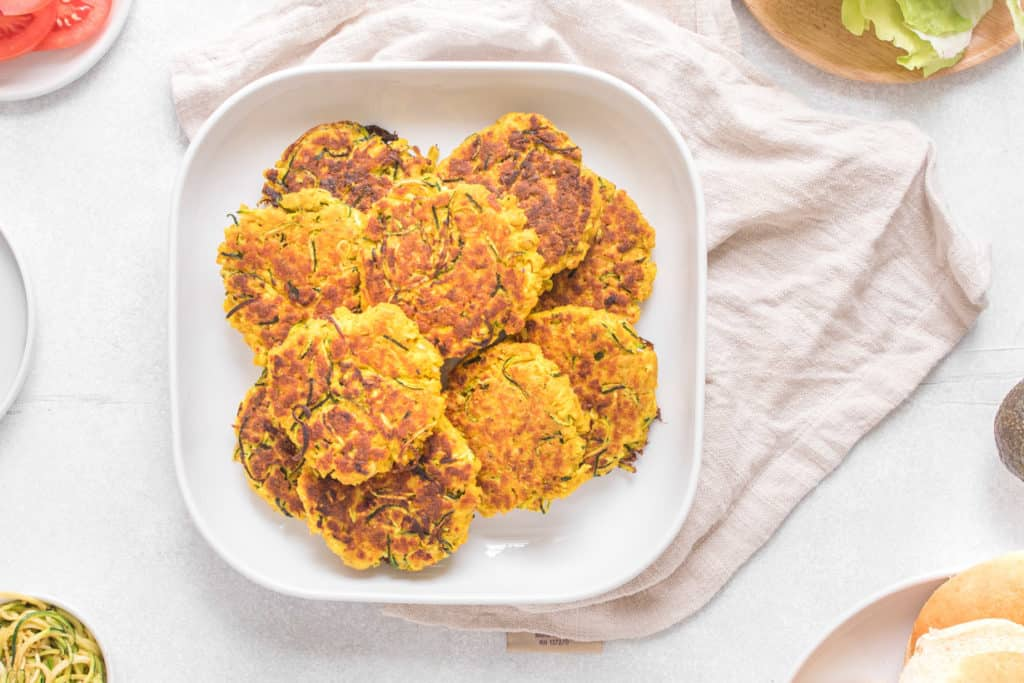 overhead shot of turmeric salmon cakes on a white plate with beige napkin