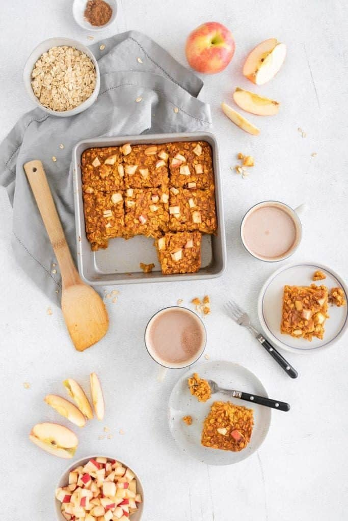 Overhead shot of apple pumpkin pie baked oatmeal with coffee and plates