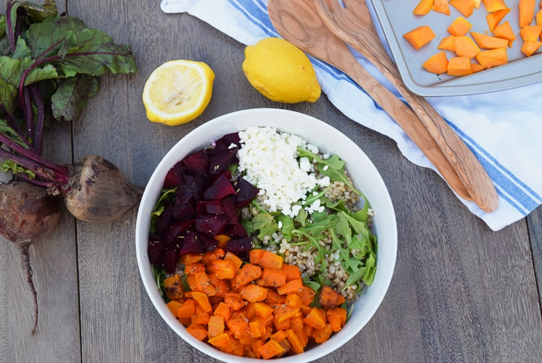 Barley salad with squash, beets, arugula and goat cheese on outdoor table with serving spoons | Bucket List Tummy