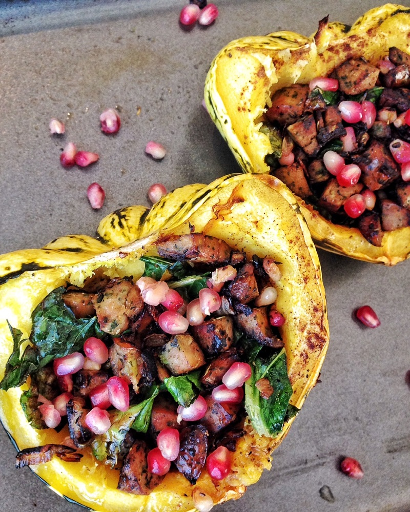 Closeup of acorn squash stuffed with pomegranate seeds, chicken sausage and kale