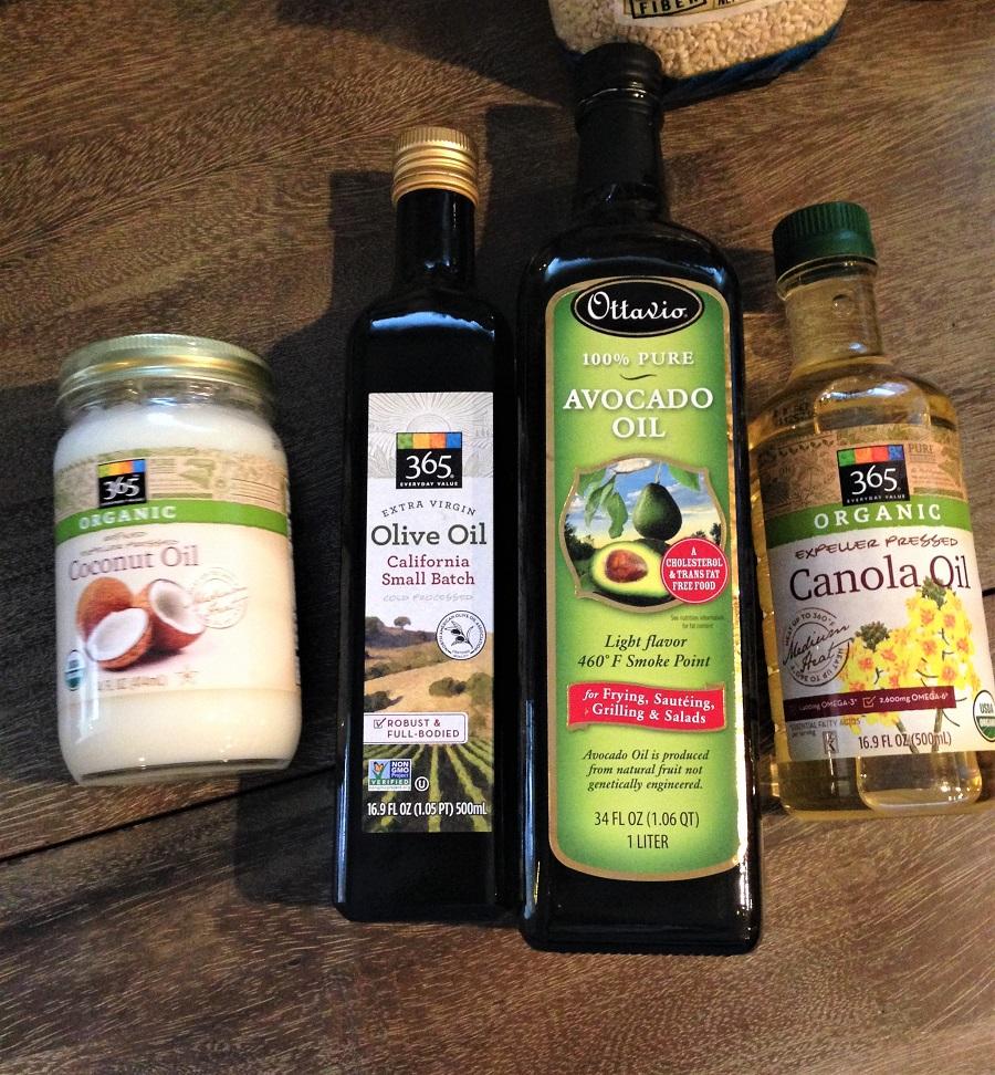 coconut oil, olive oil, avocado oil, canola oil on wooden table