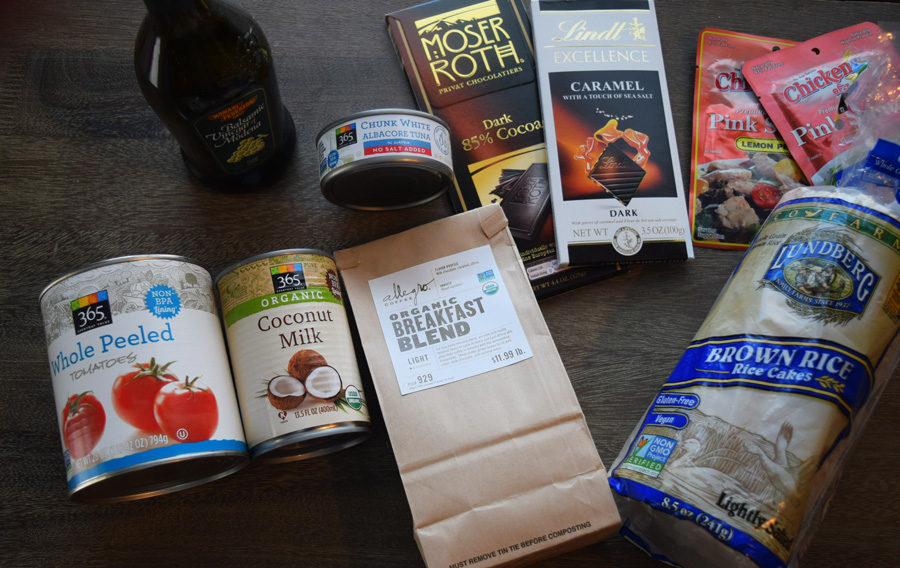 Canned goods, coffee, dark chocolate and grocery staples on wooden table