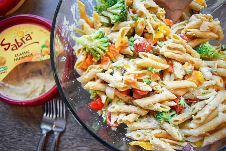 Clear bowl with veggies and hummus pasta salad