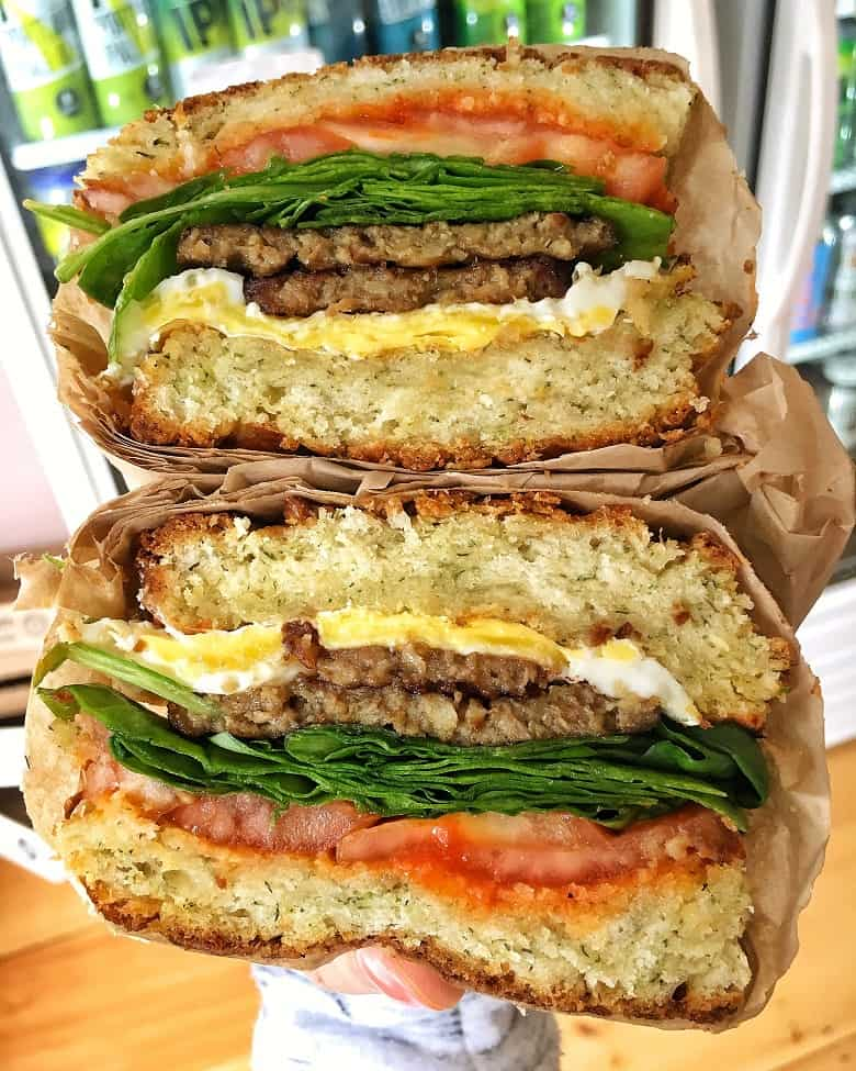 stacked breakfast sandwich with sausage, tomato, spinach and cream cheese