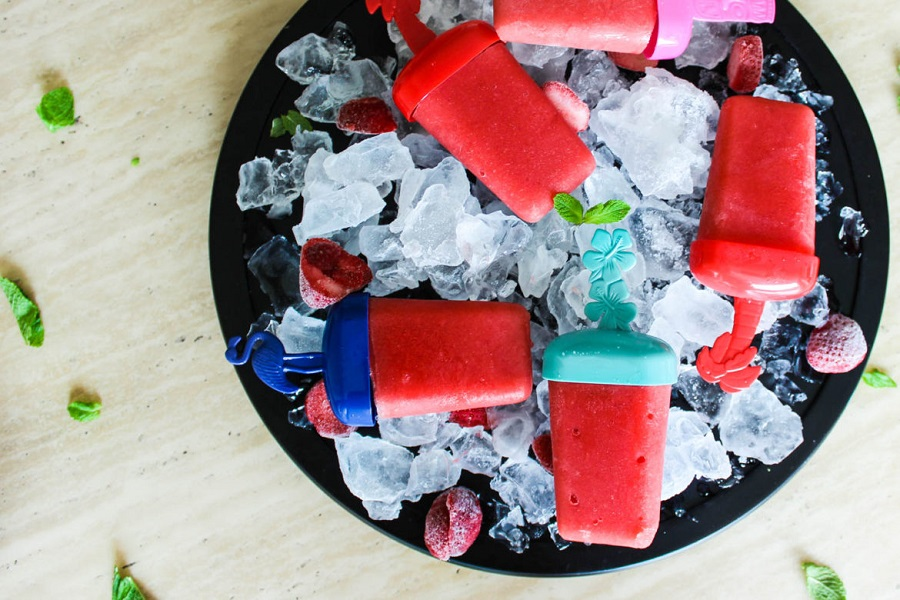 watermelon popsicles on ice in a black bowl