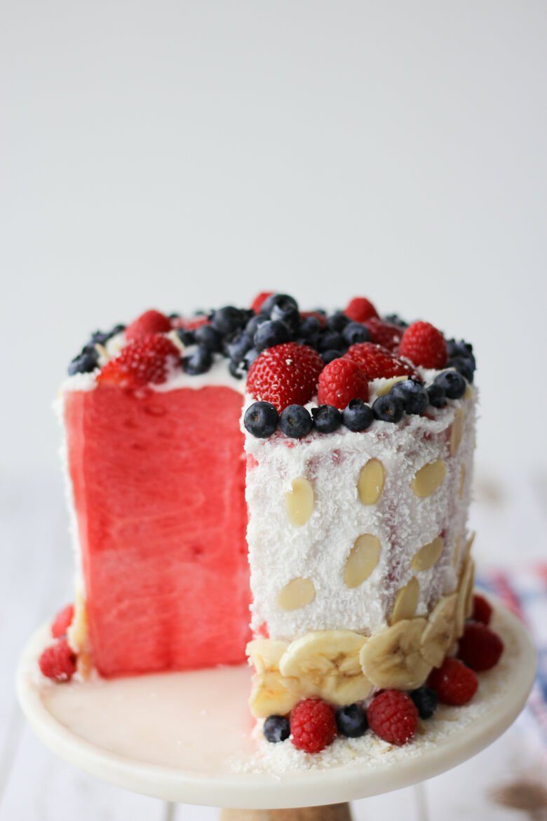 watermelon cake topped with fresh fruit on cake stand