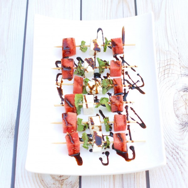 watermelon, cheese and herbs on wooden skewers on white plate with balsamic drizzle