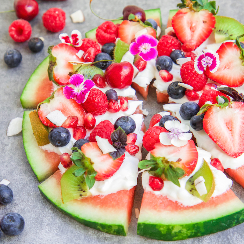 watermelon fruit pizza with whipped cream and topped with fresh fruit