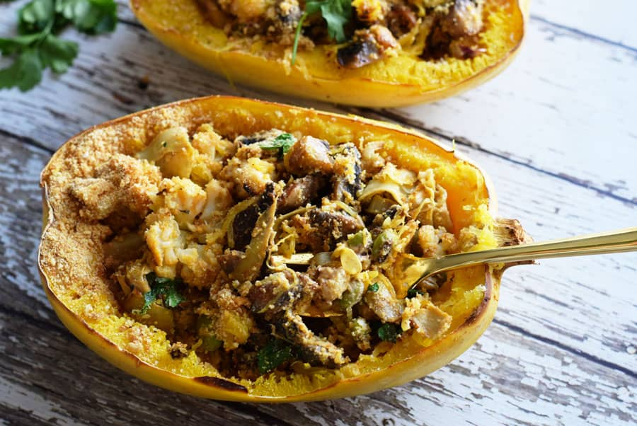 Cheesy spaghetti squash boats with fork on wooden table