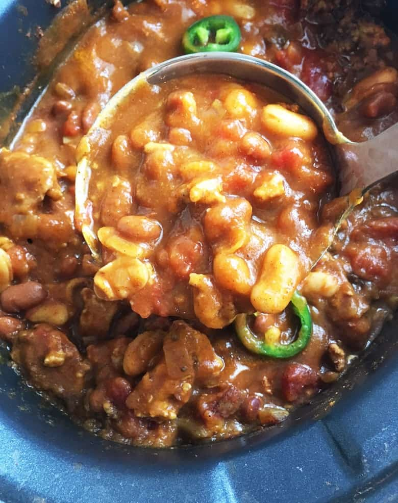 Pumpkin Chicken Chili in a crockpot with spoonful closeup