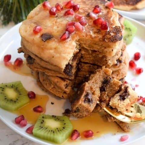 Stack of whole wheat chocolate chip gingerbread pancakes topped with pomegranate seeds | Bucket List Tummy