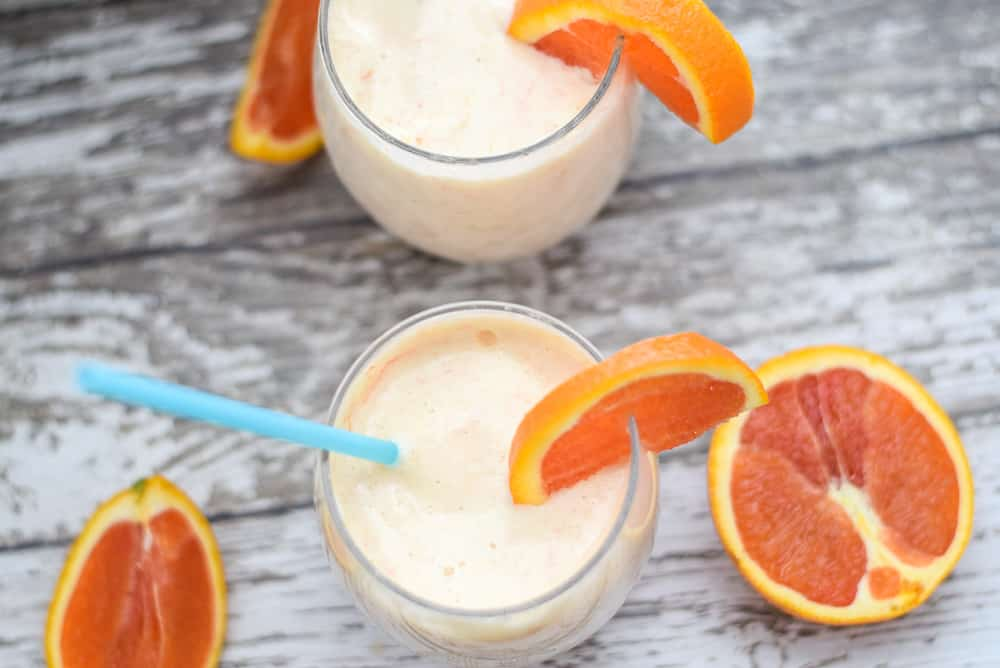 Orange Post Workout Smoothie in glass cups with a straw | Bucket List Tummy