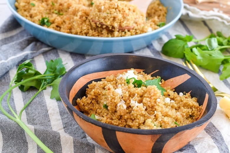 Serving bowl of cheesy quinoa surrounded by fresh herbs