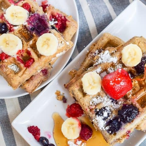 Banana oat waffles topped with berries and bananas on white plates | Bucket List Tummy
