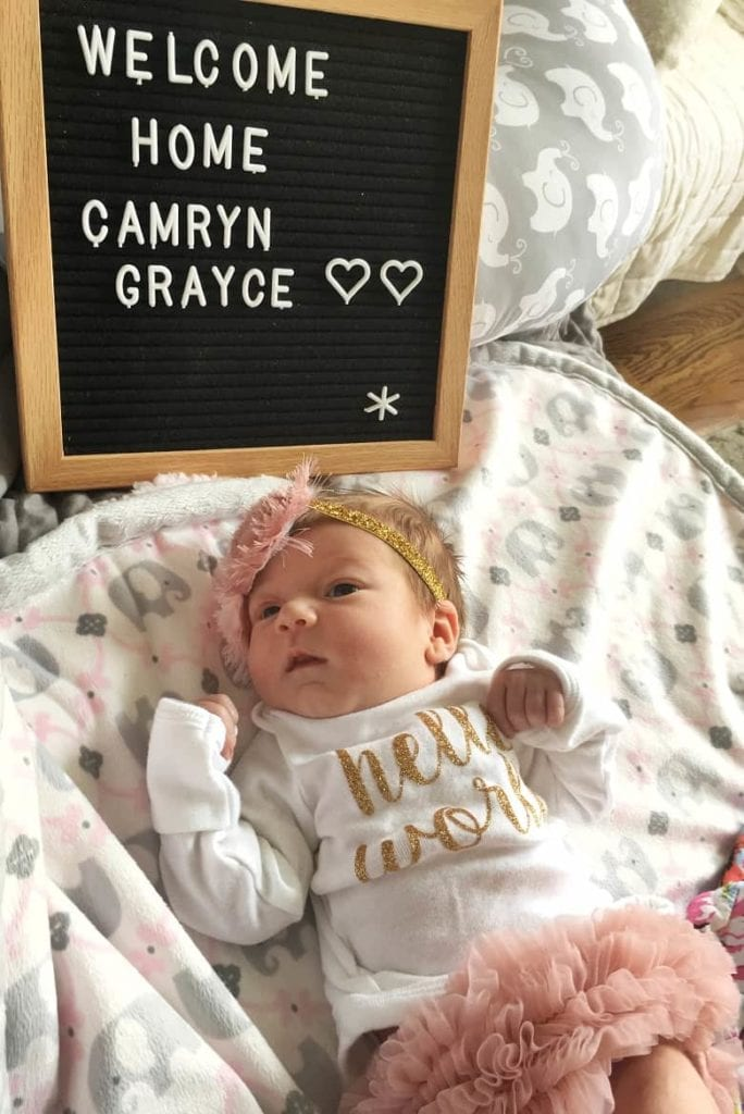 newborn laying on blanket with welcome sign