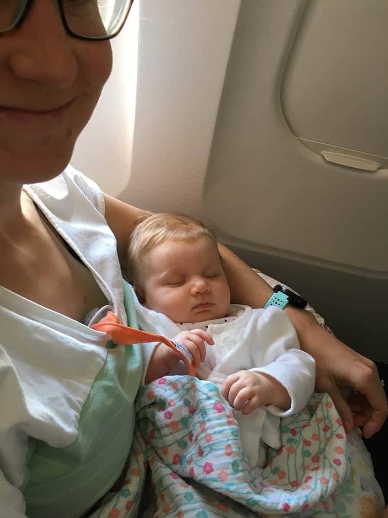 Baby sleeping in mom's arm on airplane