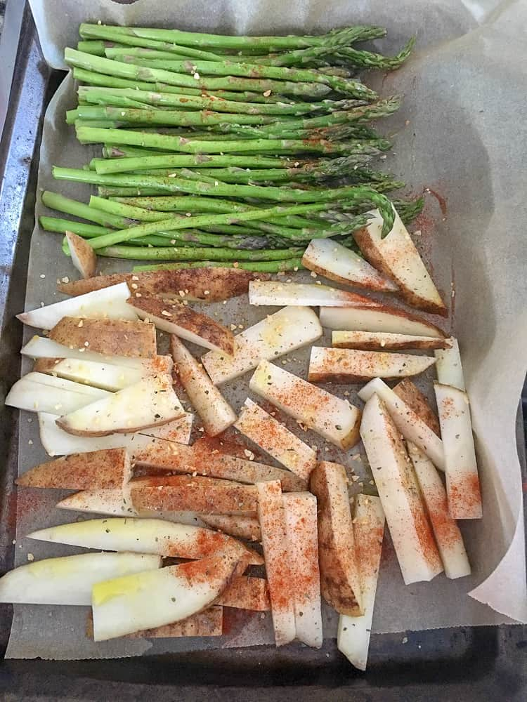 asparagus and sliced white potatoes on baking sheet and seasoned for intuitive meal prep