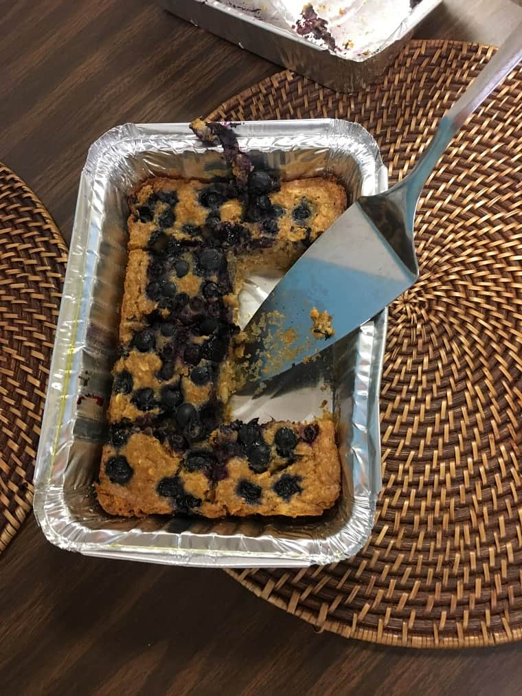 tin foil with baked oatmeal and serving spoon on wooden table