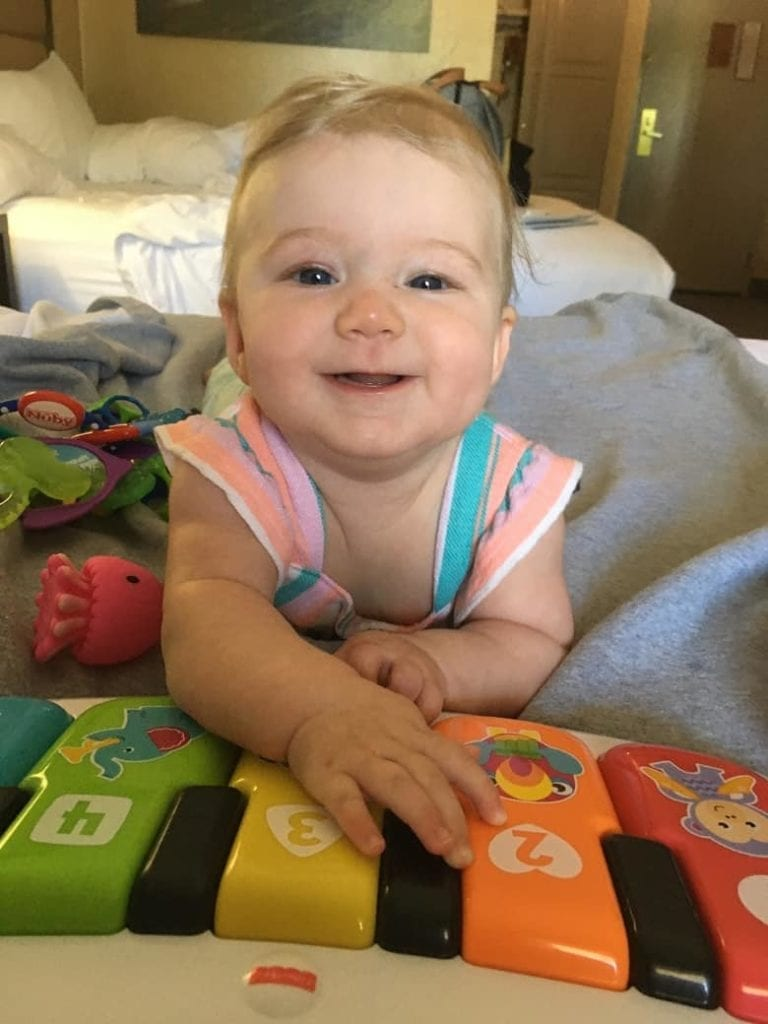 5 month old baby playing with piano toy on a bed
