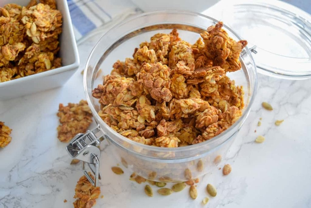 Peanut Butter Pumpkin Granola in clear container with lid open on white counter